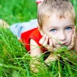 sevimli çocuk yeşil Taze çimenlerin üzerinde rahatlatıcı — Stok fotoğraf #9980759