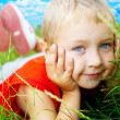 Smile of happy cute child in spring grass — Stock Photo