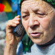 East european senior woman and mobile phone — Stock Photo