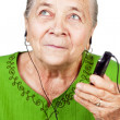 Senior woman listening music at mobile phone — Stock Photo #9980790