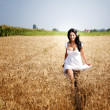 Stock Photo: Happy free woman running in grain field