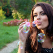 Happy woman blowing soap bubbles — Stock Photo