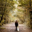 Stock Photo: Sad woman walking alone in the woods