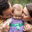 Kiss of love - parents with their baby girl - Stock Photo