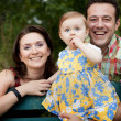 Happy family - parents and baby daughter — Stockfoto #9981630