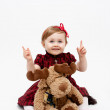 Happy baby girl with reindeer christmas toy — Stock Photo