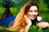 Felice giovane donna e fiore nell'erba fresca — Foto Stock