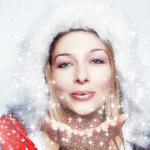 Happy winter woman blowing snowflakes — Stock Photo