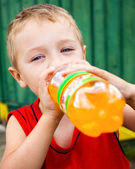 Child drinking unhealthy bottled soda — Stock Photo