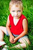 Cute serene kid on fresh green grass — Stock Photo
