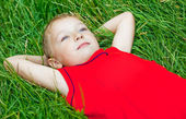 Pensive child day dreaming in fresh grass — Stock Photo