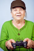 Happy senior woman playing video games — Stock Photo