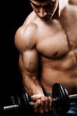 Powerful muscular man lifting weights — Stock Photo