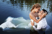 Love and passion - kiss of married couple in water — Stock Photo