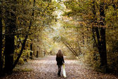 Sad woman walking alone in the woods — Stock Photo