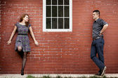 Happy couple and house with brick wall — Stock Photo