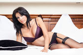 Woman in sexy lingerie posing on bed — Stock Photo