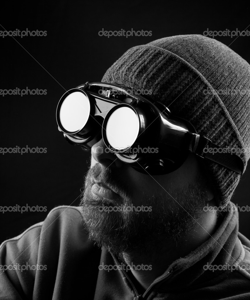 Man wearing protective goggles over black background — Stock fotografie #9981429