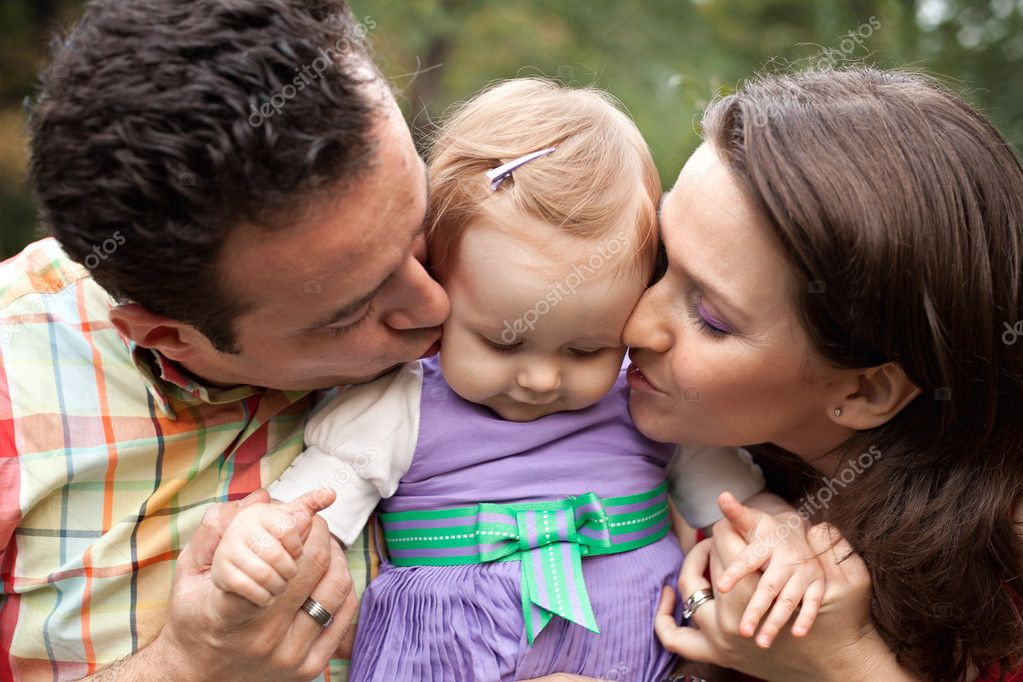 Kiss of love - happy parents with their cute baby girl — Stok fotoğraf #9981627