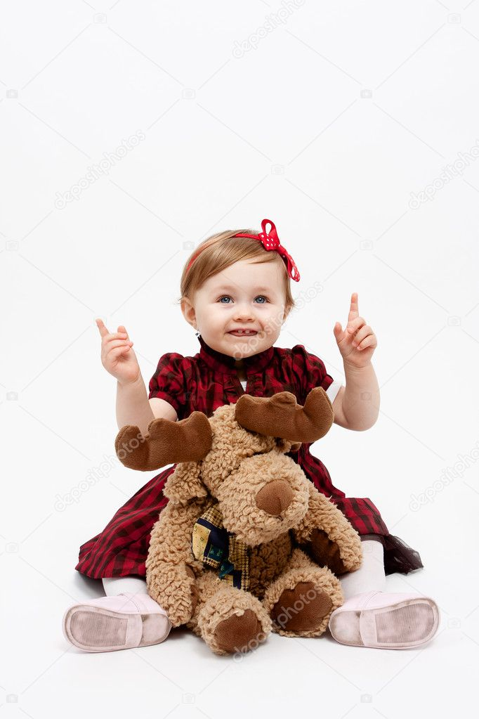 Happy baby girl with reindeer christmas present toy — Stock Photo #9981664