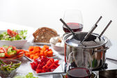 Table with fondue set and ingredients — Stock Photo