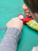 The child makes a traditional toy from different rags — Stock Photo
