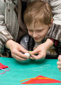 Parents help children to make traditional toys from rags — Stock Photo