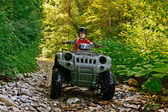 A little boy wearing a helmet riding a quad bike on the shore of a mountain river. — Stock Photo