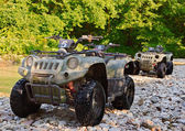 ATV's parked on the shore of a mountain river in the mountains. are resting somewhere near. — Stock Photo