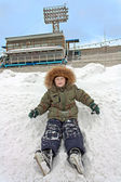The child with skates sits and have fun in a snowdrift at the stadium. — Stock Photo
