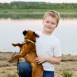 Boy play on the lake bank with dog - petit brabancon. — Stock Photo