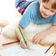 Cute dreaming child lies and draw on soft sheep fur isolated over white bac — 图库照片
