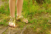 Abstract feet in the bark footwear in the grass. Ecology footwear concept. — Stock Photo
