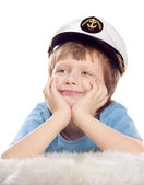 Cute dreaming child in captain cap lies on soft sheep fur isolated over white background. High key. — Stock Photo