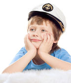 Cute dreaming child in captain cap lies on soft sheep fur isolated over whi — Stock Photo