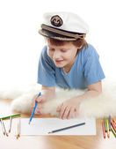 Cute dreaming child in captain cap lies and draw on soft sheep fur isolated — Stock Photo