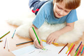 Cute dreaming child lies and draw on soft sheep fur isolated over white bac — Stock Photo