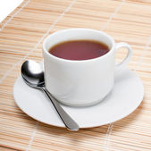 Cup of black tea with spoon on napkin isolated over white background. — Foto de Stock