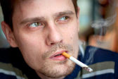 The middle-age man smokes a cigarette in the bar. Focus on the eyes. — Stock Photo