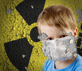 Boy in mask over old Sign of radiation on the concrete grunge station' — Stock Photo