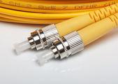 Telecommunication background.Twisted fiber optic single mode FC jack over g — Stock Photo