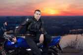 The serious Motorcyclist and its motorcycle against an evening city, the ri — Stock Photo