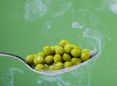 Macro photo of preserved peas vegetable in metal spoon on a light green bac — Stock Photo