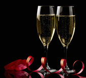 Two glasses with white wine over black background with red ribbon — Stock Photo