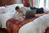 Business man working on bed — Stock fotografie