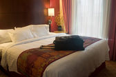 Suitcase on hotel bed — Stock Photo