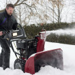 Man operating snow blower - Stock Photo