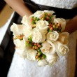 A close up image of a bride holding her beautiful bouquet - Stock Photo