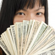 Woman's face behind money — Stock Photo