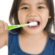 Foto de Stock  : Little asigirl brushing her teeth